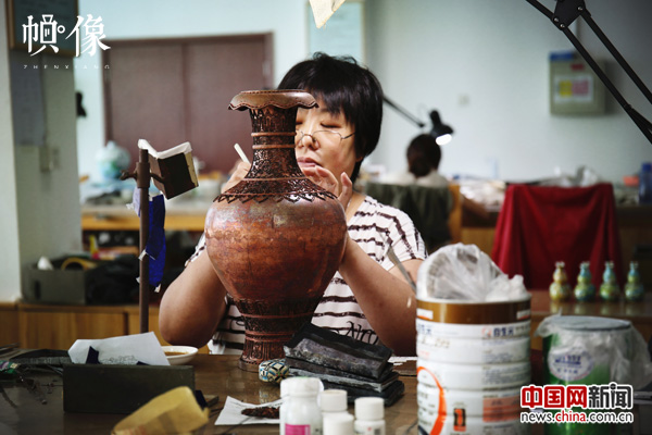 2017年9月5日,北京工美景泰蓝车间。景泰蓝工匠将制作好的铜丝按在胎型上。中国网记者 赵超 摄.JPG